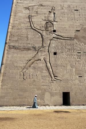 horus: El pilón en el templo de Horus. De pie 36 metros de altura, las paredes pilones están grabados con relieves que representan Ptolomeo XII Neos Dionysos sosteniendo las cabezas de sus enemigos por el pelo como Horus rompe el cráneo.