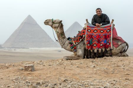 sahara desert: The sun sets over the Sahara Desert as a man rests against his camel with the Pyramids of Giza in Cairo in Egypt in the background. Editorial