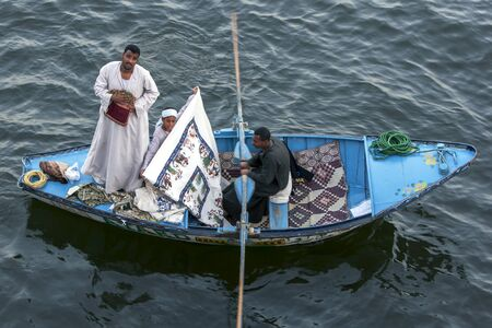 persuade: A textile salesman in a row boat tries to persuade  passengers aboard  a floating hotel to purchase some items as it waits to enter Esna Lock on the River Nile in Egypt.