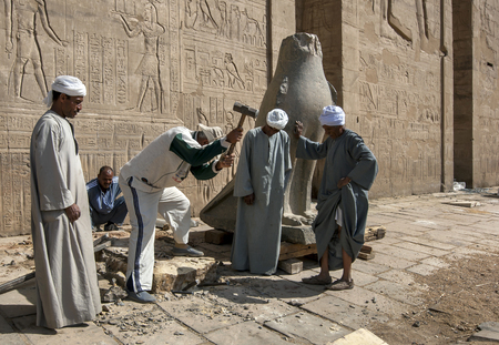 metre: Workers at the Temple of Horus at Edfu in Egypt making a new base for one of the falcons at the pylon entrance. Editorial