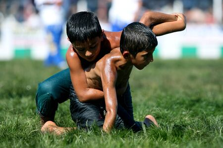 wrestlers: Young wrestlers battle for victory at the Elmali Turkish Oil Wrestling Festival in Turkey. Editorial