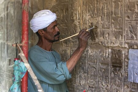 restoring: A man works on restoring a section of hieroglyphs carved into a wall at Karnak Temple in Luxor, Egypt.