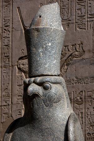 horus: The head of one of the granite statues of a falcon at the giant pylon of the Temple of Horus in Edfu, Egypt.