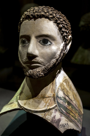 hombre con barba: A coloured limestone mask depicting a bearded man with short curly hair at the Alexandria Museum in Egypt.