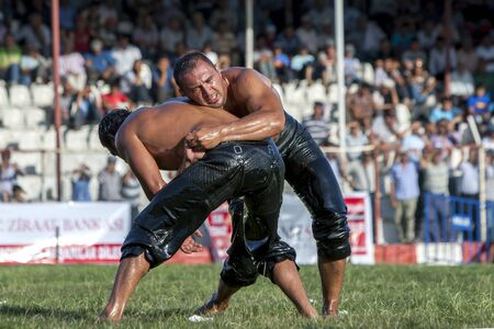the heavyweight: Heavyweight wrestlers battle for victory on the final day of competition at the Elmali Turkish Oil Wrestling Festival in Elmali in Turkey. Editorial