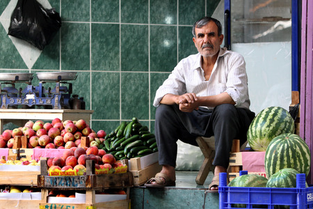 greengrocer: A greengrocer sits in his store at the Urfa (Sanliurfa) bazaar in Urfa in south eastern Turkey. Editorial