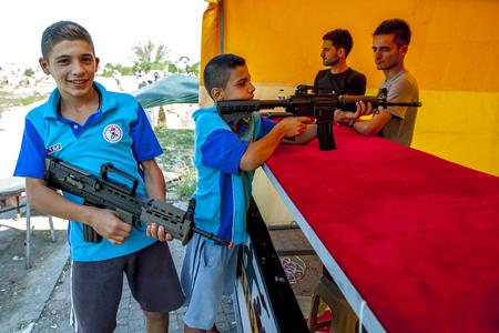 edirne: Turkish boys at a shooting gallery set up during the Kirkpinar Turkish Oil Wrestling Festival in Edirne in Turkey. Editorial