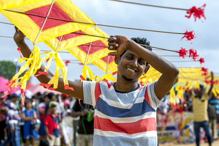 hundreds: A Sri Lankan man holds up a section of a Japanese kite on display on Negombo beach in Sri Lanka. There were hundreds of kites on the beach during the annual kite festival.