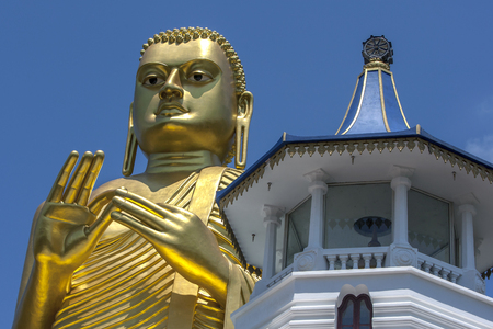 metre: The giant 30 metre high golden statue of Buddha at the Golden Temple in Dambulla in Sri Lanka. The statue is designed in the dhammachakka mudra (wheel turning pose). Stock Photo