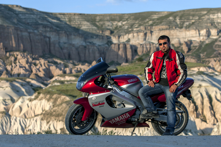 turkish man: A Turkish man sits on his motorbike near Goreme in the Cappadocia region of Turkey. Cappadocia is famous for its magnificent landscapes. Editorial