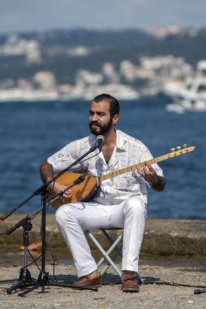 An Iranian musician playing a setar records a song adjacent to the Bosphorus at Findikli in Istanbul in Turkey.