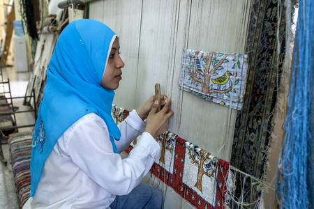 woollen: An Egyptian lady studies the design of the woollen carpet she is making in a factory in Cairo, Egypt.