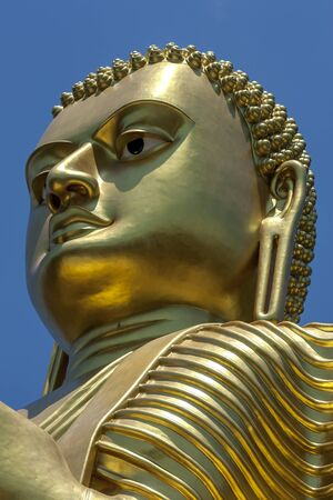 metre: The head of the giant 30 metre high golden statue of Buddha at the Golden Temple in Dambulla in Sri Lanka. The statue is designed in the dhammachakka mudra (wheel turning pose).