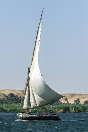 A sailing boat travels down the River Nile near Edfu in Egypt. Imagens
