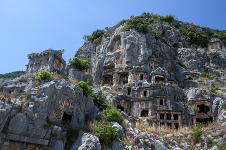 A  cliff face covered in Lycian rock-cut tombs at the ancient site of Myra at Demre in Turkey. There is evidence a settlement at Myra existed as early as the 2nd century BC. Stock Photo