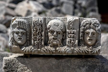Ancient stonework at Myra in Demre in Turkey depicting three human faces. Myra dates from the 2nd century BC.