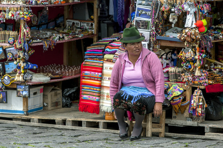 metre: A lady sits in front of her souvenir stall at El Panecillo, a 200 metre volcanic hill overlooking  Quito in Ecudor. She sells his textiles and crafted goods to the tourist market. Editorial