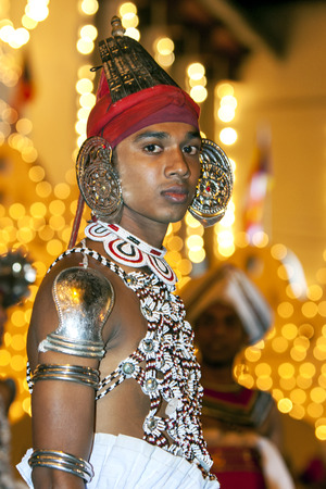 A Ves Dancer (Up Country dancers) waits to perform during the Esala Perahera in Kandy, Sri Lanka. The Esala Perahera is held to honour the Sacred Tooth Relic of Lord Buddha.