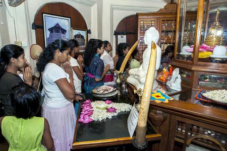 ancient relics: Buddhist worshippers pray in front of a statue of Lord Buddha inside the Buddhist Library within the Temple of the Sacred Tooth Relic in Kandy, Sri Lanka. On the far upper right of the picture is a gold casket containing ancient relics.