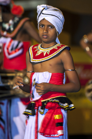 A young Cymbal Player or Thalampotakaruwo performs along the streets of Kandy during the Esala Perahera. The Esala Perahera festival runs every year in late July or early August for ten days, ending on the Nikini poya full moon.
