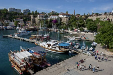 2nd century: Cruise boats docked in Kaleici Harbour in the old town section of Antalya, Turkey. In the background stands a section of the ancient Roman harbour wall dating from the 2nd century BC. Editorial