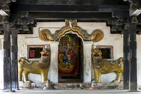 The entrance to the main shrine at Embekke Devale is located at the end of the digge (drummers pavilion) through a door guarded by lion statues.