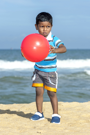 A Sri Lankan boy playing with a red ball on the sand beach in Negombo in the early morning.