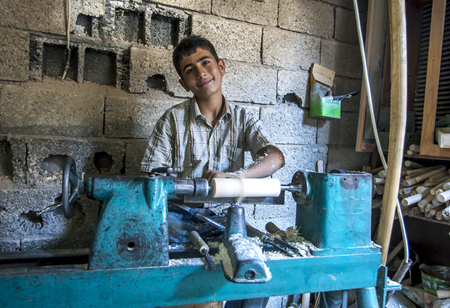 A Kurdish boy tuning a piece of wood on a lathe in a carpentry shop within the Adiyaman bazaar in eastern Turkey.