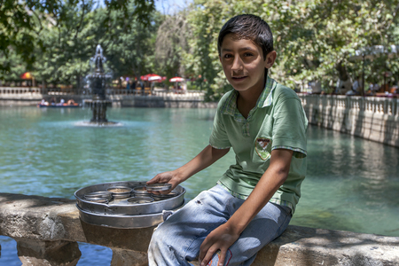 A Kurdish boy selling fish pellets sits at Ayn-i Zeliha, the second sacred pool within Golbasi Park in Sanliurfa, also known as Urfa.