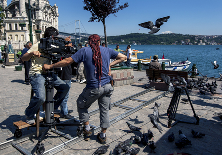 A cameraman films a scene of a man feeding the pigeons adjacent to the Bosphorus at Ortakoy in Istanbul for a Turkish soap opera (television show).