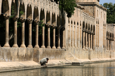 Balikli Gol (Pool of Sacred Fish) also known as Abrahams Pool in Golbasi Park in Sanliurfa in Turkey. In the background stand the arched walls of Rizvaniye Vakfi Camii.