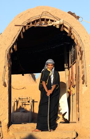 Un adolescent d'origine arabe se tient à l'entrée d'une maison de l'ancienne ville de Harran en Turquie, l'une des plus anciennes villes habitées en permanence au monde. Il porte un keffieh sur la tête.