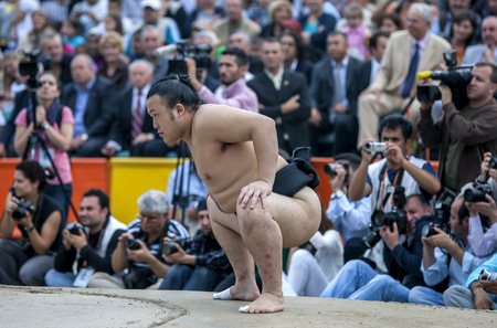 A Japanese sumo wrestler prepares for battle during an exhibition bout in Edirne in Turkey. A large crowd of Turkish people are gathered to watch the exhibition.