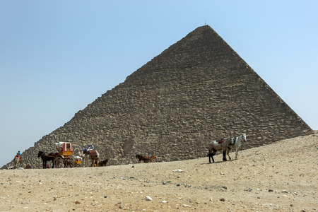 Horse and buggies wait for customers at the base of the Pyramid of Khufu at the Giza plateau in Cairo in Egypt.