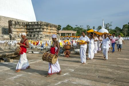 Drummers lead a group of Buddhist pilgrims performing a Kapruka Poojawa Ceremony around the base of the Ruwanwelisiya Dagoba (Ruvanvelisaya) at Anuradhapura in Sri Lanka. Redakční