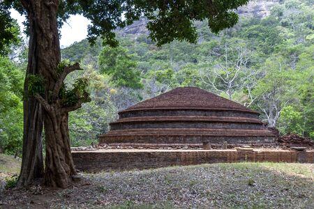 The ancient red brick Buddhist dagoba at Kaludiya Pokuna Forest and Archeological Site near Sigiriya in Sri Lanka. This site dates to the 2nd century BC.