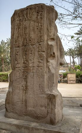 Hieroglyphs on the pink granite Triad of Memphis stone at the ancient Egyptian capital of Memphis at Mit Rahina in Egypt. It dates from the New Kingdom. 写真素材