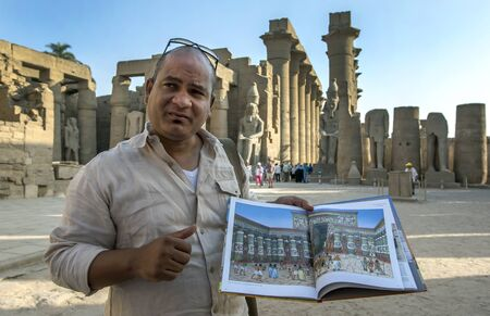 An Egyptian tour guide displays a picture book showing how the Courtyard of Ramesses ll at the Luxor Temple (Temple of Amun-Ra) at Luxor in Egypt would have appeared in the 15tn century BC. Editorial