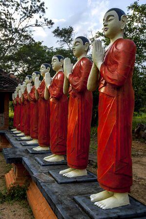 A row of Buddhist monk statues stand within the Pidurangala Buddhist Temple at Sigiriya in Sri Lanka. Stock fotó