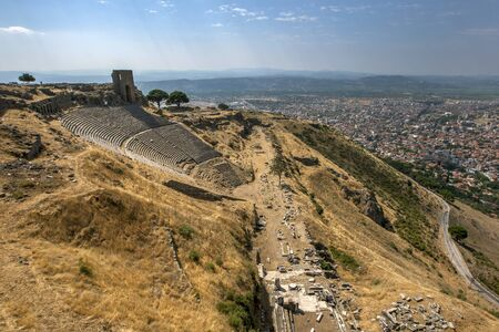 The ruins of the Roman theatre and The Temple of Dionysus (foreground) at the ancient site of Pergamum which sits above the modern town of Bergama in the Izmir Province of western Turkey. The city dates from the 5th century BC but gained importance during the Hellenistic Age from 323 BC onwards.