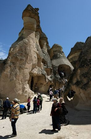 Tourists gather around a unique series of volcanic rock formations known as a fairy chimneys at Pasabagi near Zelve in the Cappadocia region of Turkey.These caves could have been a church or a home in ancient times.