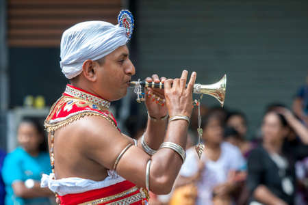 A Trumpet Blower performs along a street in Kandy during the Day Perahera, the final parade of the Buddhist Esala Perahera festival at Kandy in Sri Lanka. Editorial