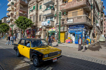 A taxi drives down a road past apartment buildings in a suburb of Alexandria in Egypt.