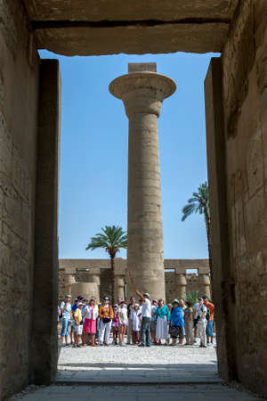 Tourists stand adjacent to the remaining column of the Kiosk of Taharqa within Karnak Temple (Temple of Amun) at Luxor in Egypt.Taharqa was a 25th Dynasty pharaoh. Editorial