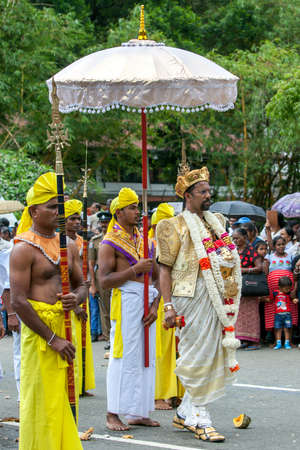 A  Temple Custodian is shielded with an umbrella by an attendant during the Day Perahera, the final parade of the Buddhist Esala Perahera festival at Kandy in Sri Lanka. Editorial