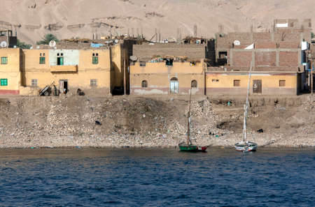 Apartment buildings sit adjacent to the bank of the River Nile north of Esna Lock in Egypt on a hot afternoon.