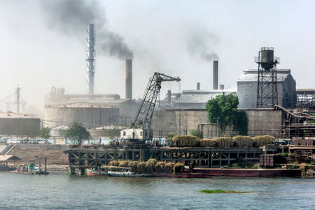 Smoke billows from the chimneys stacks of factories which line the bank of the River Nile south of Luxor in Egypt. In the foreground sugar cane sits loaded on railway wagons at the dock.
