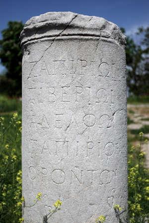 A stone column with engraved script at the ancient Roman Bath ruins at Ankara in Turkey.