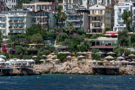 A view looking from the Mediterranean Sea towards the rock beach of the seaside town of Kas in Turkey.