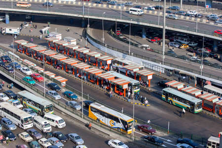 Traffic comes to a crawl on the roads of downtown Cairo in Egypt in the late afternoon. In the centre stands a bus station.